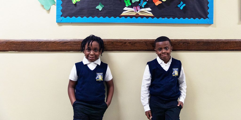Smiling students standing in hallway.